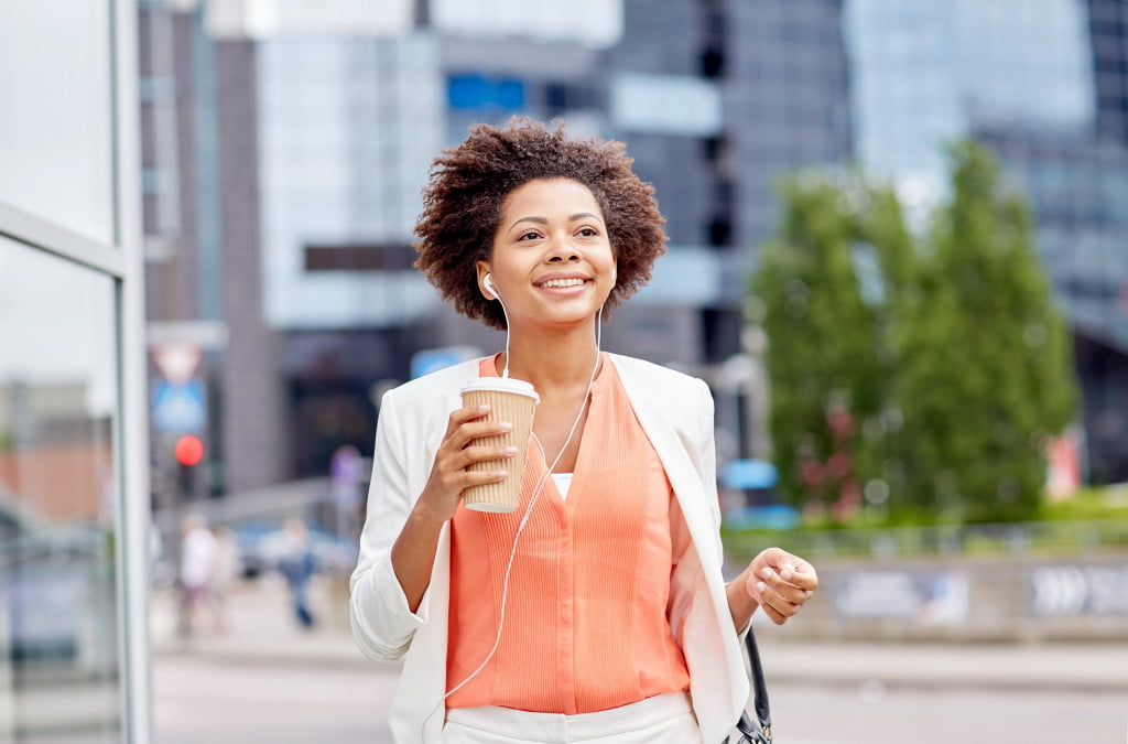 Female walking with a cup of coffee and earphones