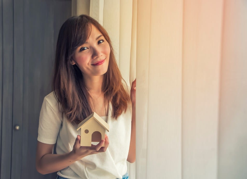 woman holding small house model