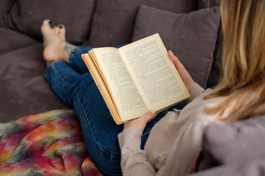 person reading a book in the sofa