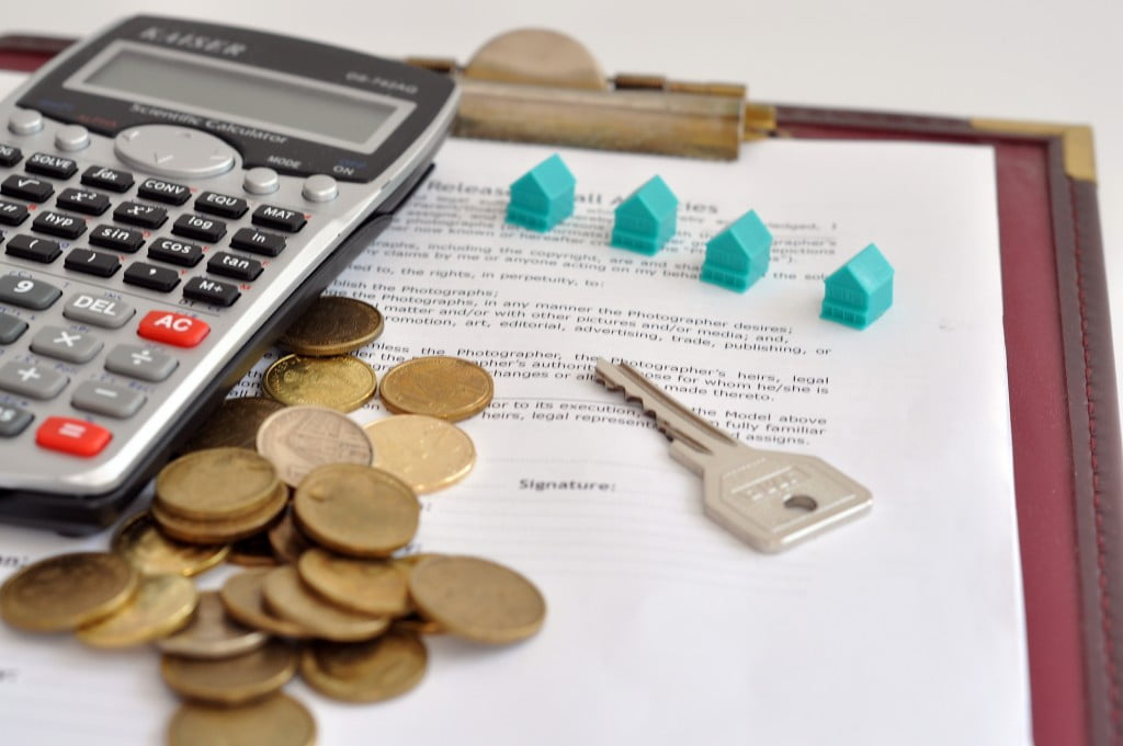 miniature homes, coins, and calculator on top of a document