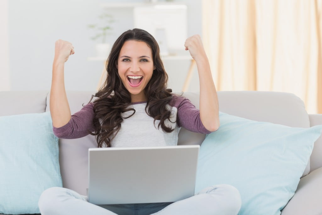 happy woman sitting on a sofa with a laptop