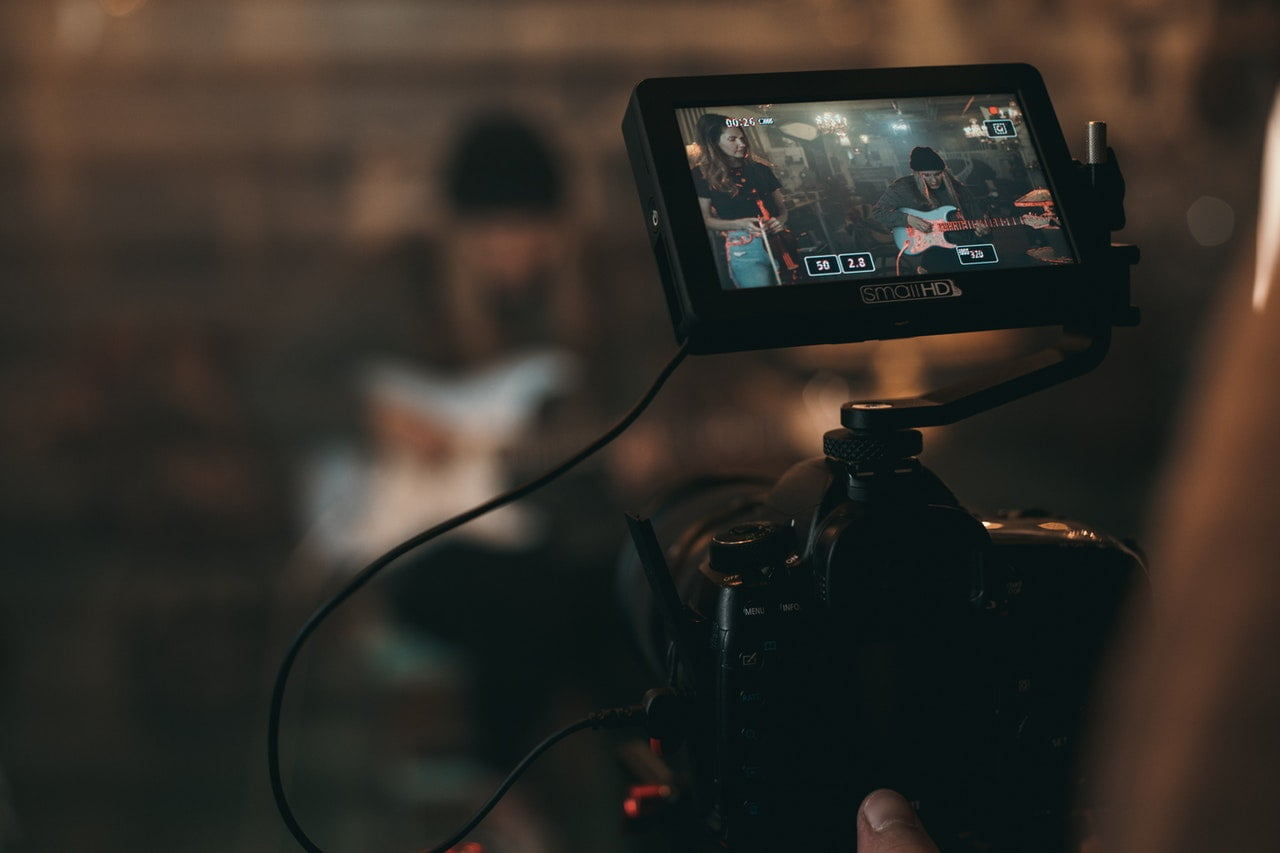 person taking a video recording of a band